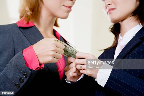 Mid section view of two businesswomen holding a dollar bill