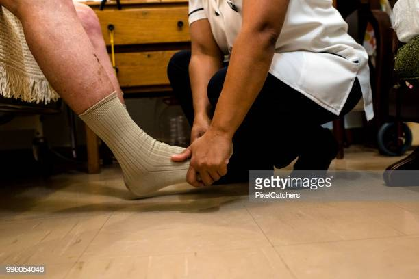 mid shot of female nurse carefully massaging senior man's feet in retirement home - outpatient care stock pictures, royalty-free photos & images