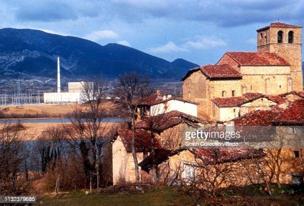 Mid shot of medieval stone buildings and leafless trees with the Ebro river Santa Maria de Garona Nuclear Power Plant and mountains in the background...