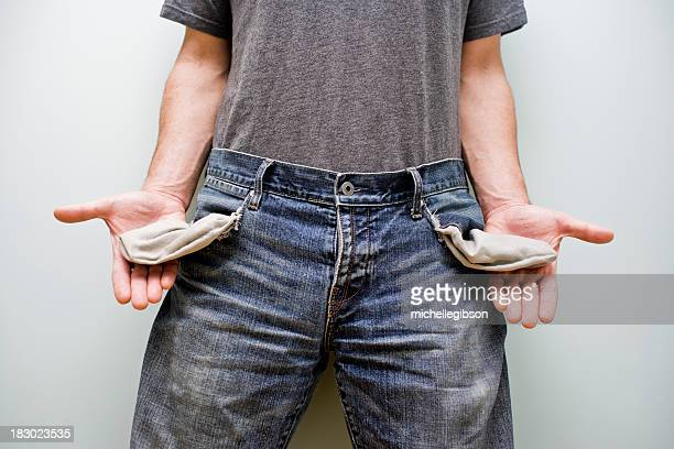 Mid view of man pulling out his empty jeans pockets for debt