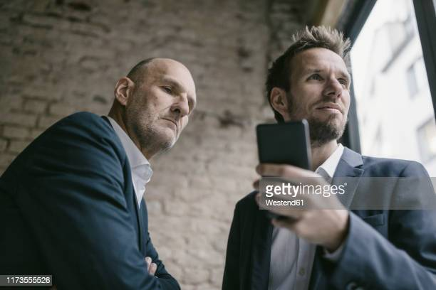 mid-adult businessman holding cell phone with  senior businessman behind him - successor stock pictures, royalty-free photos & images