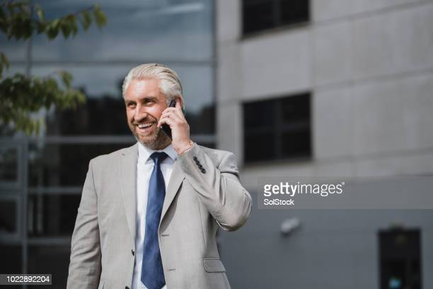 mid-adult businessman talking on the phone - st. james' park newcastle upon tyne stock pictures, royalty-free photos & images
