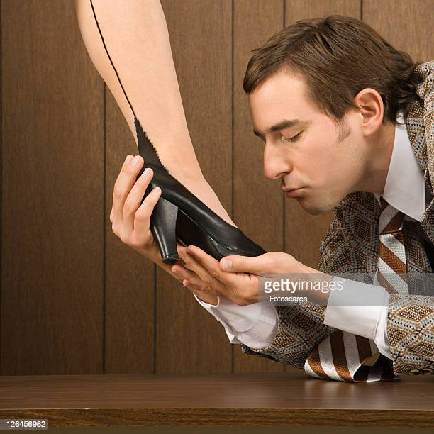 Mid-adult Caucasian male holding Caucasian female shoe and preparing to kiss it.