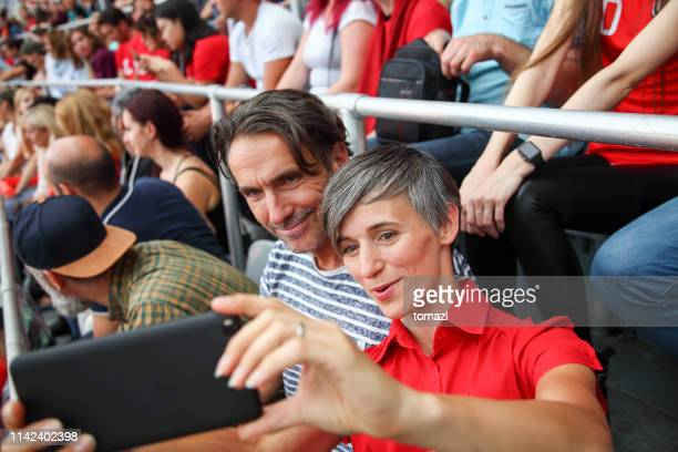 mid-adult couple at footbal match making a selfie - sports event stock photos and pictures