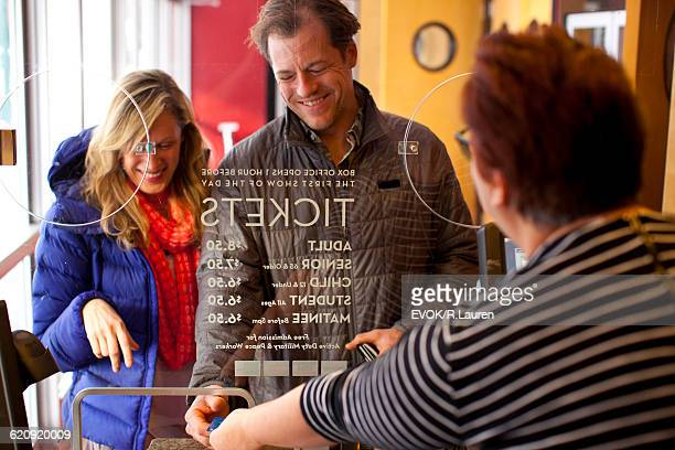 mid-adult couple buying tickets at theater box office - hygiaphone photos et images de collection