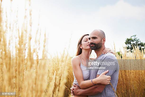 Mid-adult couple cuddling in field
