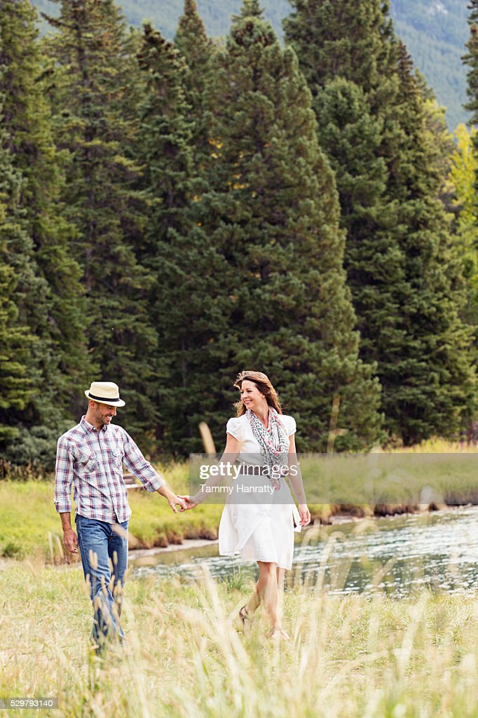 Mid-adult couple holding hands and relaxing while walking at lakeshore : Foto de stock