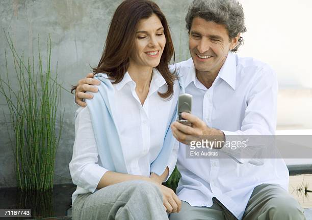 Mid-adult couple, man showing woman cell phone