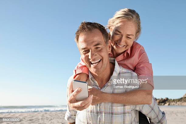 Mid-adult couple on beach using cell phone