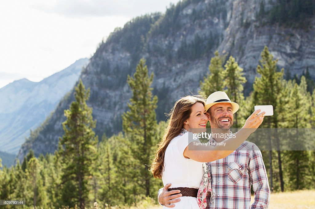 Mid-adult couple photographing themselves in mountains : Stock Photo