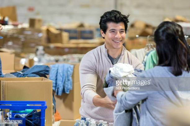 mid-adult couple share a smile as they pass clothes at a charity concert - non profit organization stock pictures, royalty-free photos & images