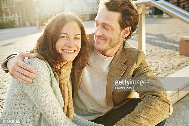 Mid-adult couple sitting on pavement