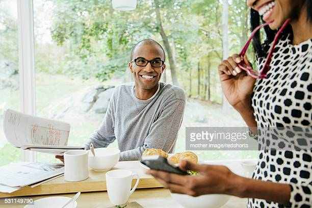 Mid-adult heterosexual couple eating breakfast and text messaging