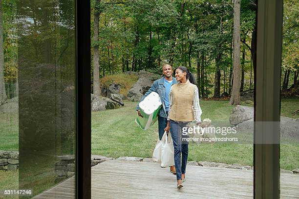 mid-adult heterosexual couple returning home with shopping bags - toilet paper tree stock pictures, royalty-free photos & images