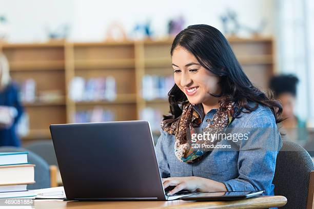 Mid-Adult Hispanic woman studying in college library with laptop computer