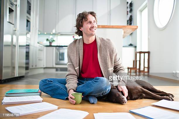 Mid-adult man doing paperwork on floor, while dog is sleeping next to him