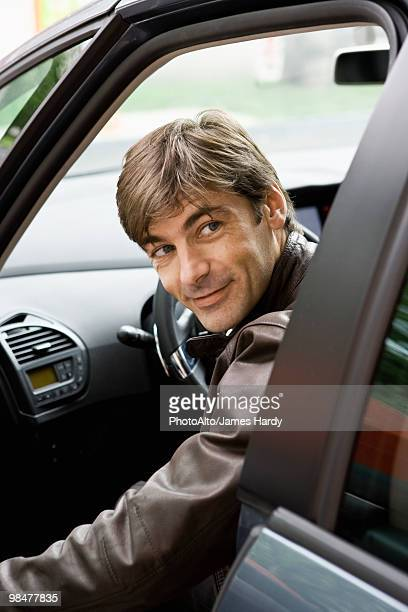 Mid-adult man getting into car, looking over shoulder before shutting door