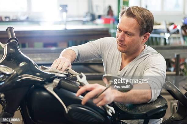 Mid-adult man polishing vintage moped
