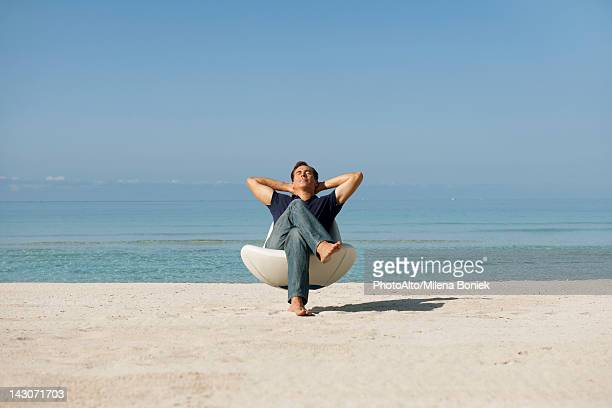 Mid-adult man relaxing in armchair on beach with eyes closed