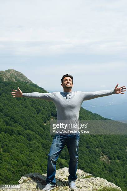 Mid-adult man standing at edge of rock with arms outstretched, mountainscape in background