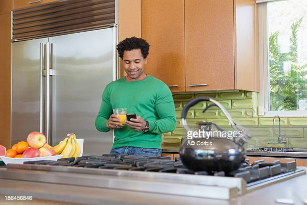 Mid-adult man standing in kitchen with glass of juice in hand and cell phone