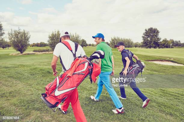 mid-adult men talking on golf course - golf stock pictures, royalty-free photos & images