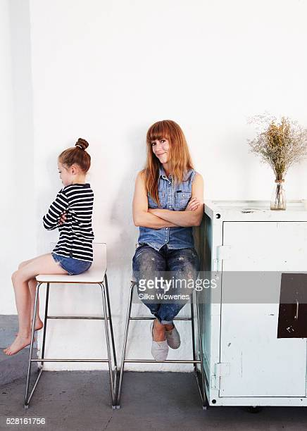 mid-adult mother having an argument with her sulking daughter