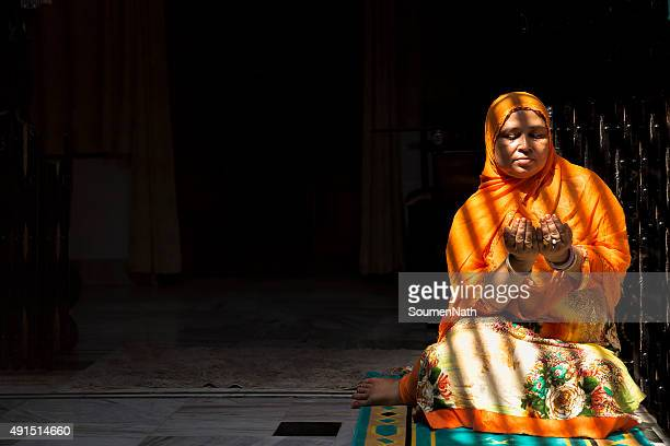 mid-adult muslim woman praying, with folded hands - muslim woman darkness stock photos and pictures