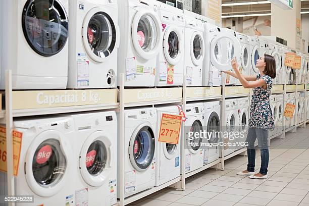 Mid-adult woman choosing washing machine in store
