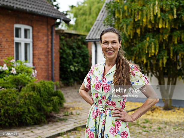 mid-adult woman in floral dress, smiling in back garden - floral pattern dress stock pictures, royalty-free photos & images