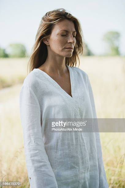 Mid-adult woman in tunic standing outdoors with eyes closed