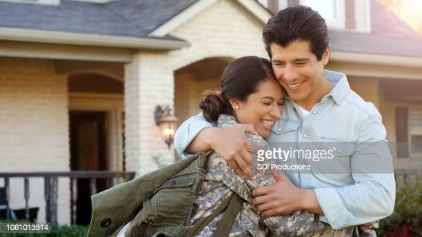 mid-adult woman in uniform is pulled into hug by a mid-adult man. - military spouse stock pictures, royalty-free photos & images