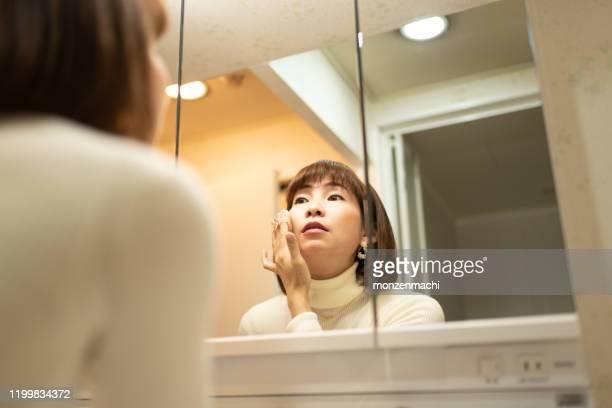 家の中で化造る中年の女性 - 35 39歳 ストックフォトと画像