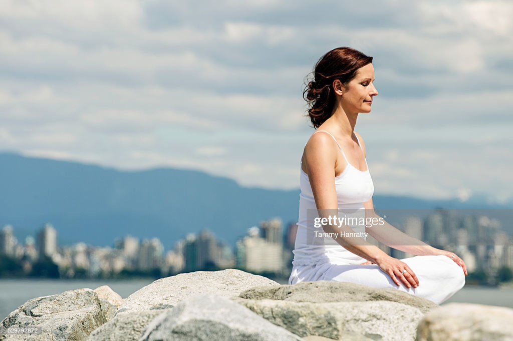 Mid-adult woman meditating while practicing yoga at sea : Stock-Foto
