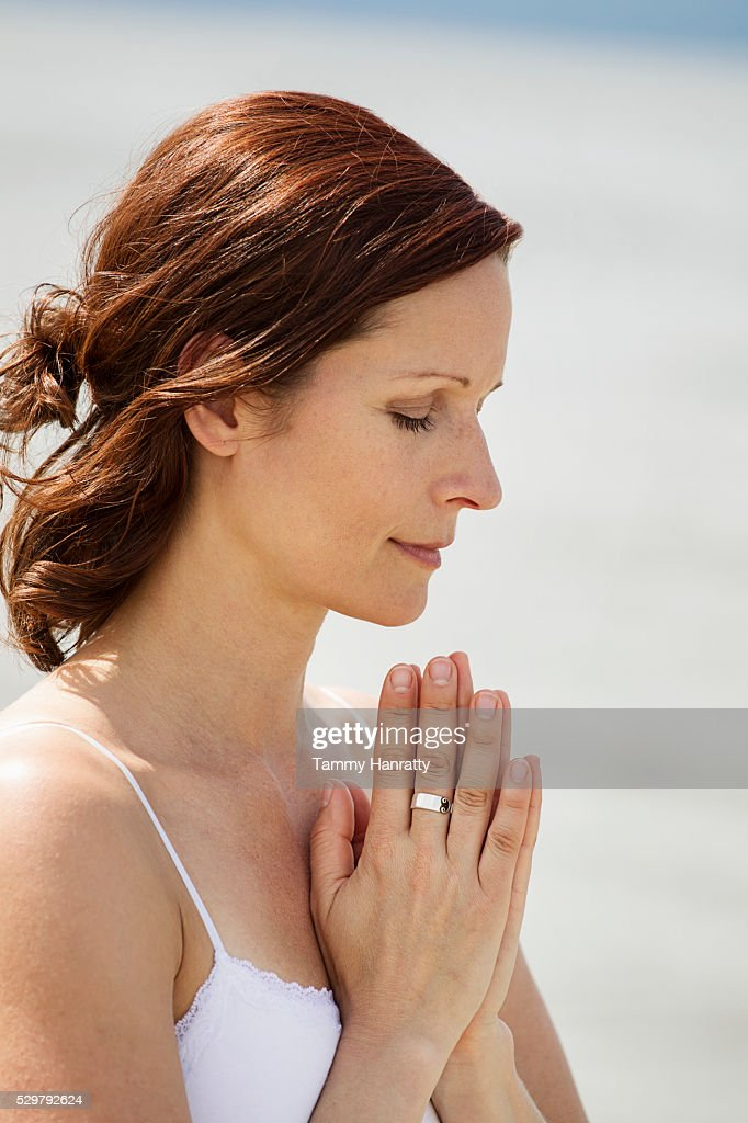 Mid-adult woman meditating while practicing yoga : ストックフォト