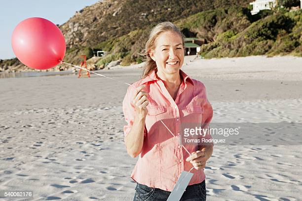 Mid-adult woman on beach with balloon, smiling