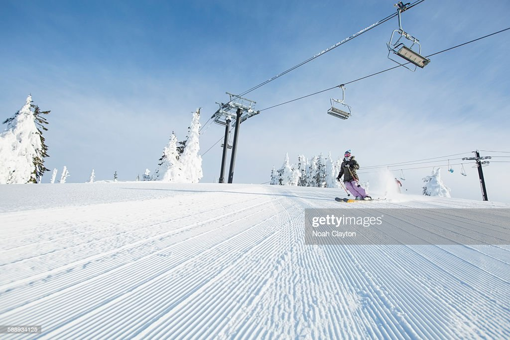 Mid-adult woman on ski slope under cable car : Stock Photo