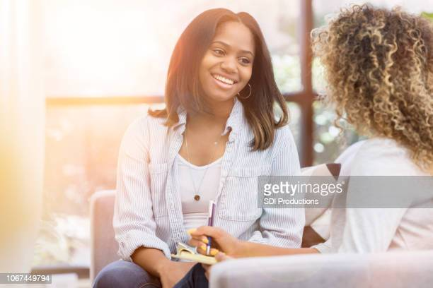 a mid-adult woman smiles during a therapy session in a bright office - guidance stock pictures, royalty-free photos & images
