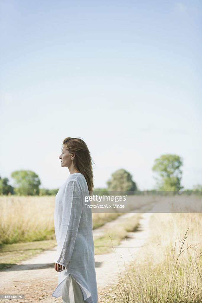 Mid-adult woman standing in field : Stock Photo