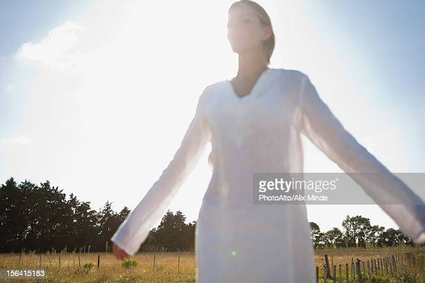 Mid-adult woman standing in field with eyes closed and arms outstretched