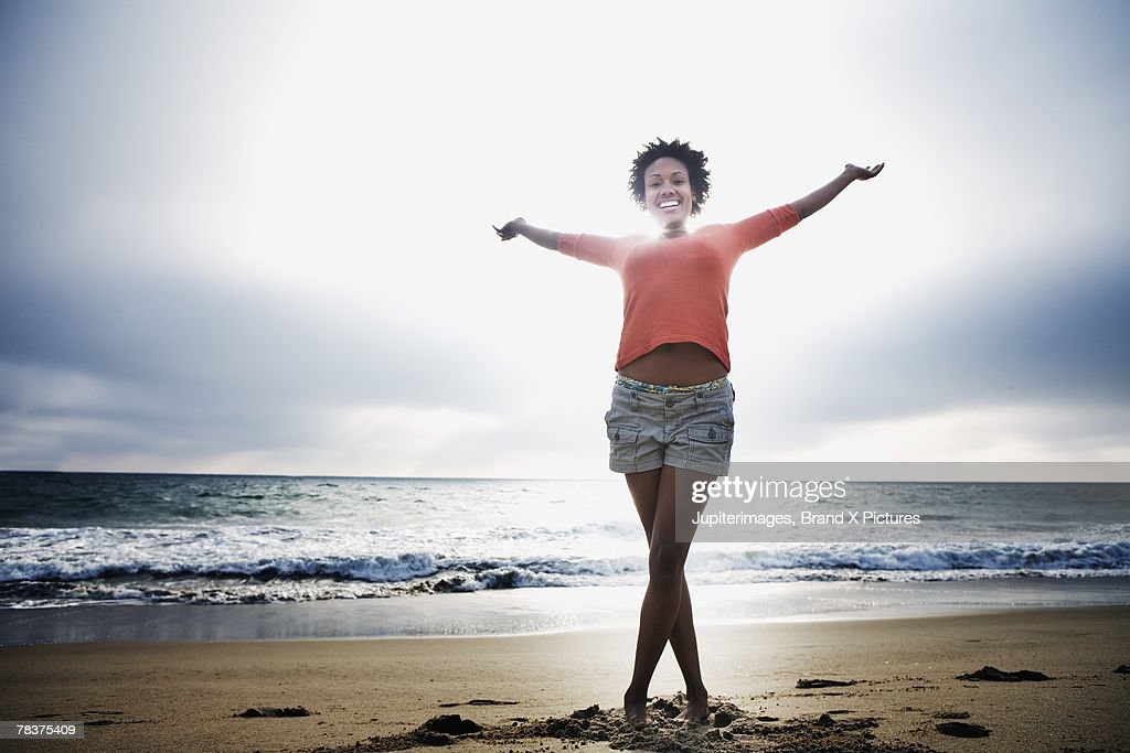 Mid-adult woman standing on beach with arms outstretched : Stock Photo