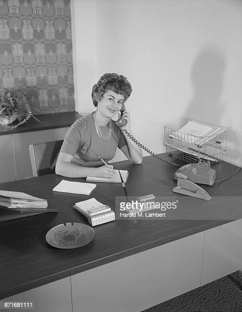 mid-adult woman talking on telephone and checking document - {{ contactusnotification.cta }} stockfoto's en -beelden