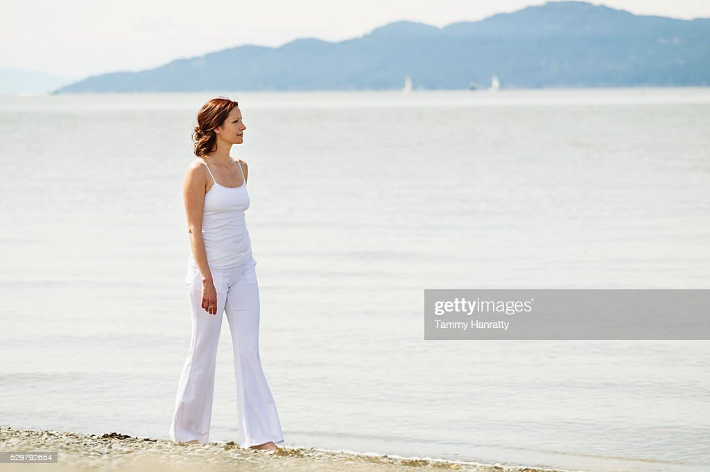 Mid-adult woman walking on beach : Bildbanksbilder