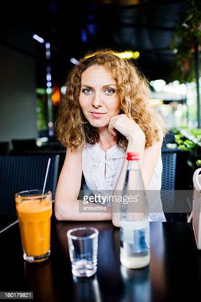 Midadult Woman with Carrot and Celery Juice in a restaurant