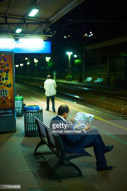 Mid-age man reading newspaper on bench while waiting train. Night scenery.