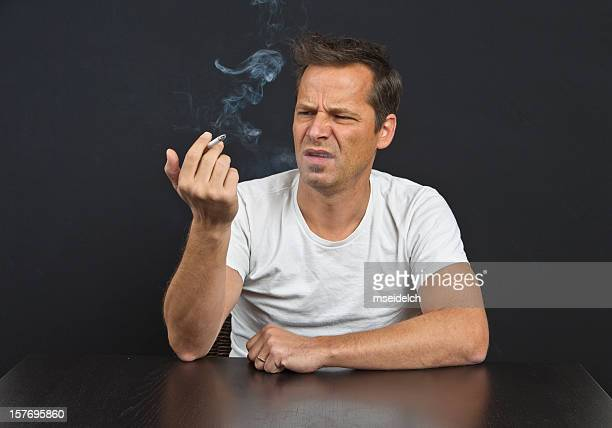 Mid-age man smoking disgusted on black background