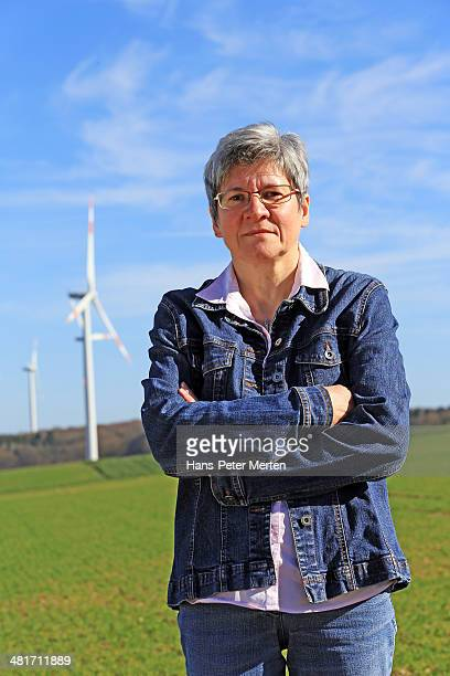 mid-age woman in front of windturbines