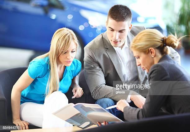 Milieu couple âgé de choisir une voiture en voiture salon.