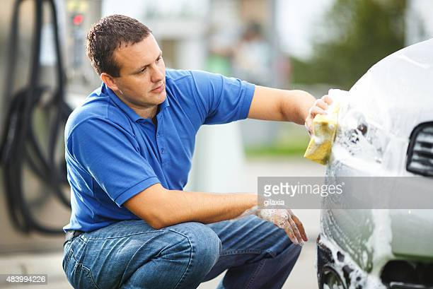 Mid-aged man washing his car outdoors.