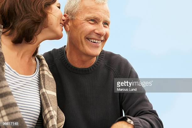 mid-aged woman whispering to man